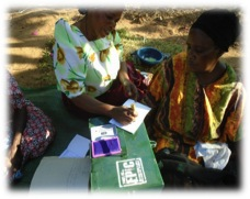 VSL Passbook being stamped following savings process in one of our This Is EPIC Uganda VSL groups.